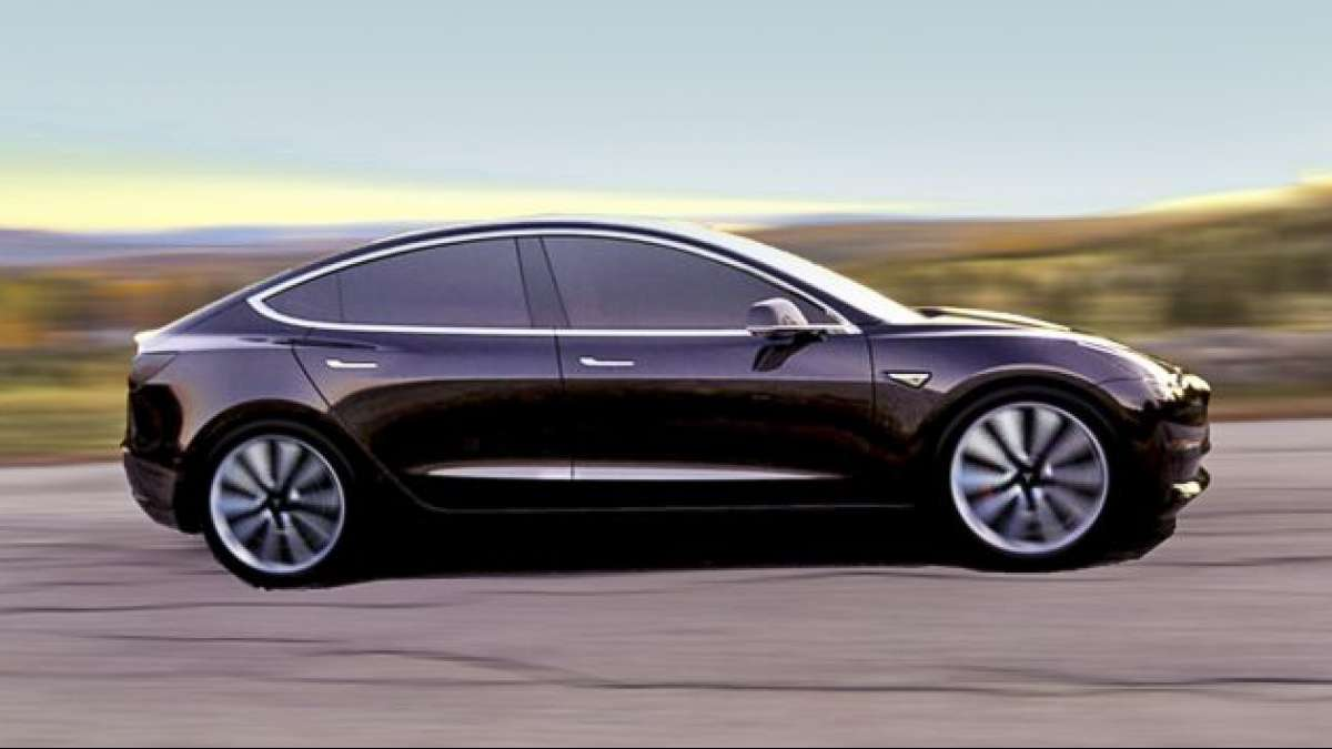 CEO Elon Musk shows off First Tesla Model 3 electric car rolling off production line