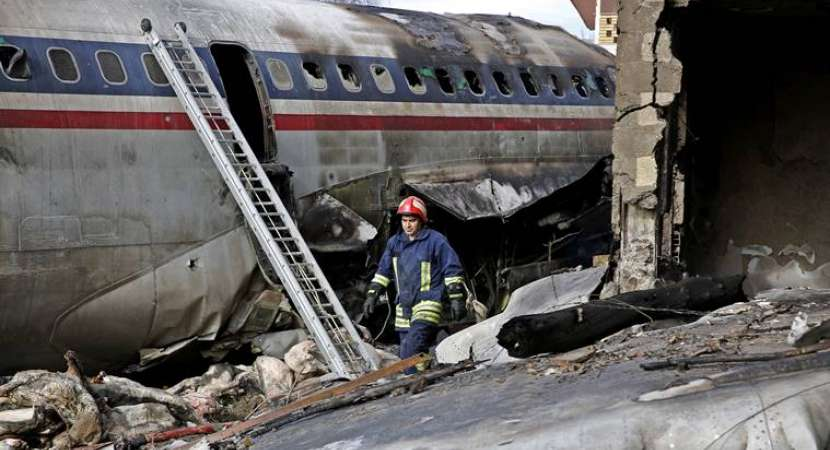 An Iranian rescue worker at the site of a Boeing 707 cargo plane crash, at Fath Airport about 40 kilometers (25 miles) west of Tehran, Iran, Monday, Jan. 14, 2019.